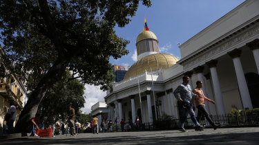 People walk outside the National Assembly in Caracas, Venezuela, which has two rivals claiming to be its president.