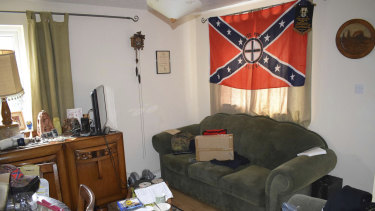 Swastika cushions and a Ku Klux Klan flag hanging in the lounge of the home of Adam Thomas and Claudia Patatas.