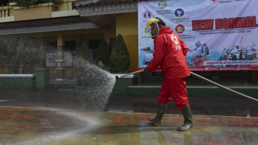 A member of Indonesia Red Cross sprays disinfectant in an attempt to help curb the spread of the coronavirus at a school in Jakarta.
