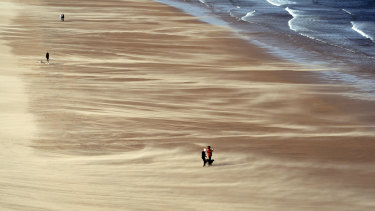People walk along Tynemouth Beach on the North East Coast of England, as forecasters warn about strong storm winds across the region.