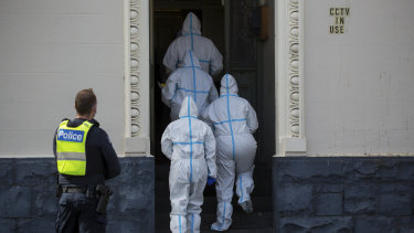 Healthcare workers enter Hambleton House in Albert Park on Sunday morning, after an outbreak and reports of quarantine breaches by residents.