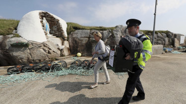 Garda police officer Pat McIlroy and Nancy Sharkey, Presiding Officer for Gola Island, arrive on the island off the coast of Donegal with a ballot box on Thursday.