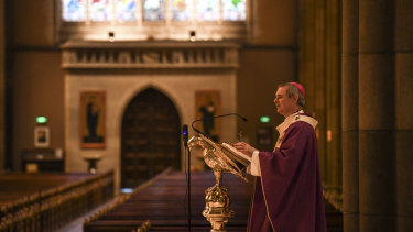 Melbourne Archbishop Peter Comensoli prepares to give the homily at Sunday mass to empty pews at St Patrick's Cathedral.