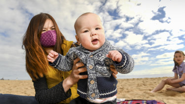 Mei Ling Tallis with her seven-month-old baby Charlie and eight-year-old daughter Kylie at Elwood Beach on Monday.