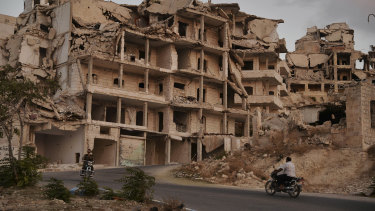 Motor cycles ride past buildings destroyed during the fighting in the northern town of Ariha, in Idlib province, Syria.