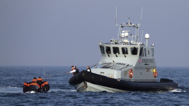 A British Border Force vessel assists a group of people thought to be migrants on board from their inflatable dinghy in the English Channel.