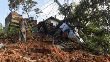 A resident carries a disassembled bed after rescuing it from a landslide-damaged home in Belo Horizonte.