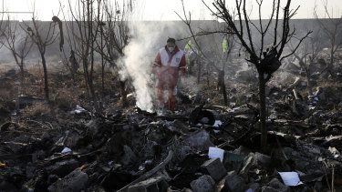 Rescue workers at the scene of the crash site near Tehran.