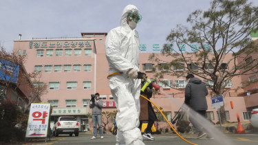 A worker wearing protective gears in front of the Daenam Hospital in Cheongdo, South Korea the southeastern city where a surging viral outbreak, largely linked to a church in Daegu.