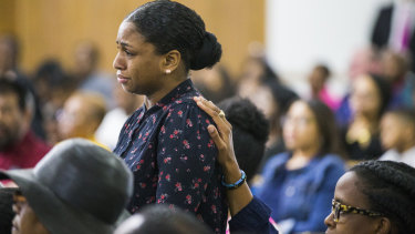Cynthia Johnson, Botham Jean's girlfriend, stands up as she is comforted by another churchgoer during a prayer service for Jean.