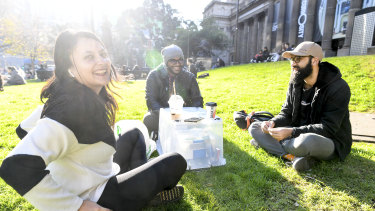 Carlton D'Silva (right), pictured having a coffee with friends Akshaya and Kenneth outside the State Library, said he had seen some people not abide by social distancing, but none within his smaller group of friends.