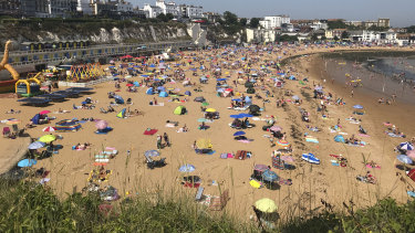 People flock to Broadstairs beach in Kent, England, on Thursday.