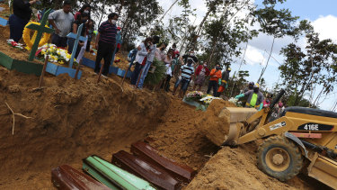A backhoe buries coffins in a common pit at the Nossa Senhora Aparecida cemetery in Manaus.