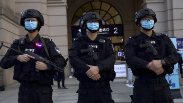 Police officers wearing face masks to protect against the spread of new coronavirus stand guard outside of Hankou train station ahead of the resumption of train services in Wuhan on Wednesday.