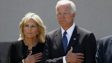 Former vice-president Joe Biden, right, and his wife Jill Biden, pause with hands over their hearts as they watch a military honour guard place the casket of Senator John McCain into a hearse.