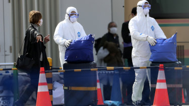 Officials in protective suits help a passenger disembark from the Diamond Princess cruise ship.