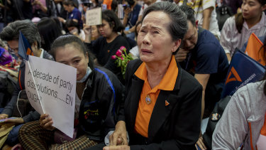 A supporter of Thailand's Future Forward Party cries as they watch a live television broadcast of a court verdict at their party's headquarters in Bangkok on Friday.
