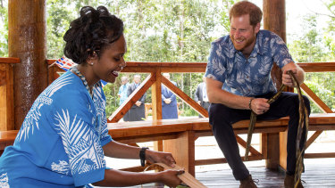 The Duke of Sussex watches a demonstration of traditional mat weaving.