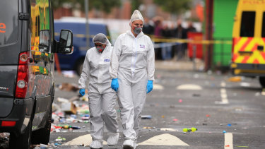 Forensic officers at the scene in the Moss Side area of Manchester, England, where several people have been injured after a shooting, early Sunday.