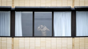 A man plays up to the camera while undergoing hotel quarantine at The Holiday Inn at Melbourne Airportin February.