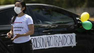 """With a sign that reads in Portuguese """"Bolsonaro Traitor,"""" a former supporter of Brazil's President Jair Bolsonaro joins a protest in Rio on Sunday."""