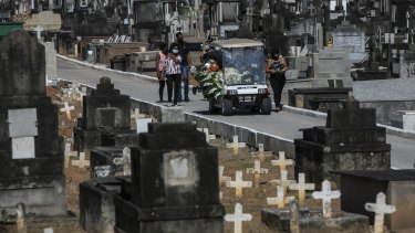 Relatives attend the burial of 71-year-old Jose Abelardo Bezerra, who died from COVID-19 related complications, in Rio de Janeiro on Thursday.