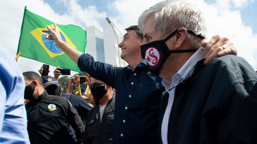Brazilian President Jair Bolsonaro and Secretary of Institutional Security and Brazilian Army General Augusto Heleno wave to supporters.