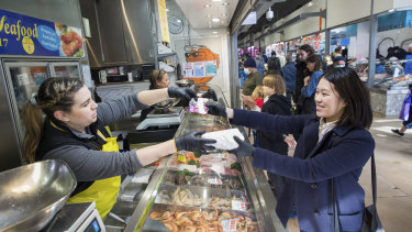 Silvia from Gazza's Gourmet Seafood at Queen Victoria Market accepts a food voucher from an international student.