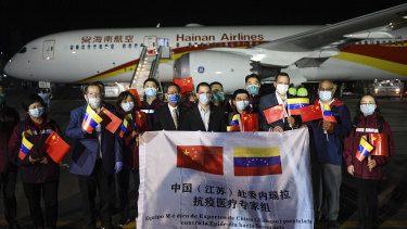 Venezuelan and Chinese officials repeat the PR exercise as a medical team arrives from China in La Guaira, Venezuela.