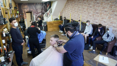Customers have their hair cut at the Unique Traditional barber's in Whitley Bay, England on Monday.