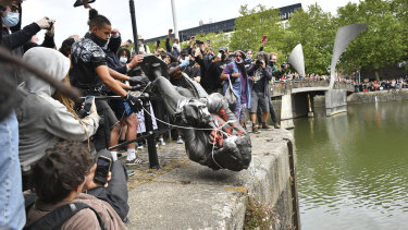 Protesters throwing a statue of slave trader Edward Colston into Bristol Harbour on June 7.