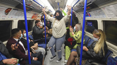 People ride a Northern Line train in London after the 10pm pub and restaurant curfew that has been prompted by the spread of COVID-19.