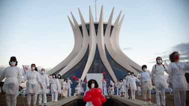 A person holds red balloons during a performance by artists from the Federal District in honour of the victims of coronavirus at Brasília's Cathedral in Brazil.