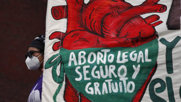 """A woman holds a banner reading, in Spanish, """"Legal, safe, and free abortion, legalise and decriminalise abortion now, for the independence and autonomy of our bodies,"""" as abortion-rights protesters demonstrate in front of the National Congress in 2020."""