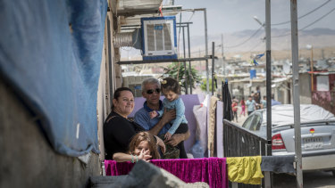 A family stands outside their home in the Domiz camp for Syrian refugees, near the town of Dohuk, northern Kurdistan, Iraq.