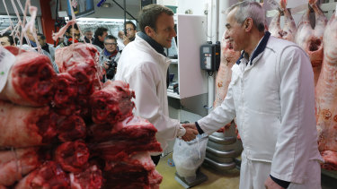 French presidential candidate Emmanuel Macron, left, shakes hands with a butcher as he visits the meat pavillon at the Rungis wholesale food market, south of Paris in May 2017.