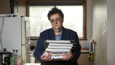 Davidh Digman in his Seaford, Melbourne home, holding his robo-debt files.
