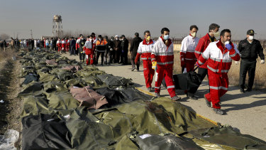 Rescue workers carry the body of a victim of the Ukrainian plane crash to a row of body bags, in Shahedshahr, south-west of Tehran, Iran, on Wednesday.