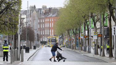 A man pushes a pram across an almost deserted O'Connell Street in Dublin's city centre.