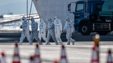 Emergency workers walk from the Diamond Princess cruise ship at Daikoku Pier on Tuesday.