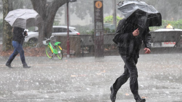 Pedestrians brave the rain in Sydney's CBD on Monday.