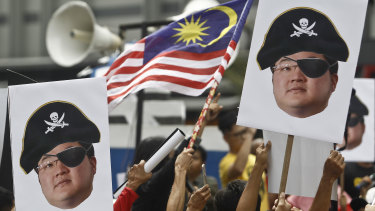 Protesters hold portraits of Jho Low during a protest in Kuala Lumpur, Malaysia.