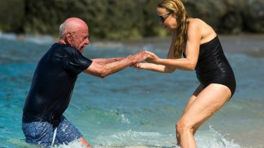 Take my hand: Hall helps Murdoch from the surf.