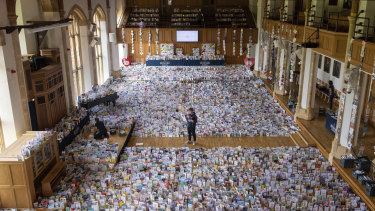 Captain Tom's grandson Benjie stands in the Great Hall of Bedford School where more than 125,000 birthday cards have been sent from around the world.