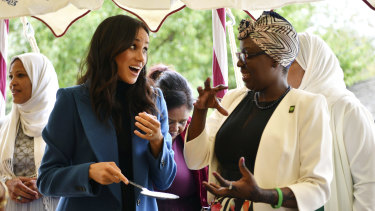Meghan, the Duchess of Sussex, with one of the women behind a charity cookbook during a reception at Kensington Palace in September.