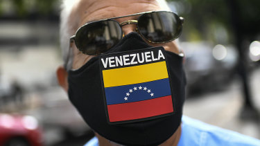 A man wears a face mask with the Venezuela flag, amid the spread of the new coronavirus, as he waits for hours to fill up his car at a state-run oil company PDVSA as station in Caracas.