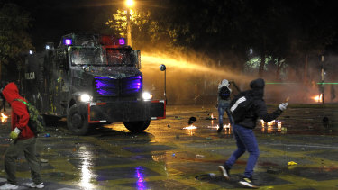 Protesters throw objects to an anti-riot tank as it sprays water during a national strike on May 5 in Medellin, Colombia.