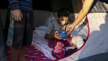 Angel, 10, who broke his left leg playing soccer and is treated by Dr Elisondo in a migrant camp in Matamoros, Mexico.