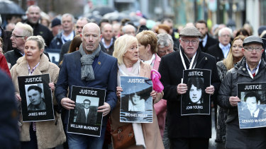 Families hold photographs of the victims of Bloody Sunday and march through the Bogside in Londonderry on Thursday.