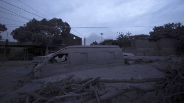 A vehicle sits partially buried in volcanic ash spewed by the Volcan de Fuego.